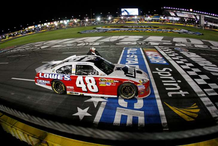 Jimmie Johnson, driver of the No. 48 Lowe's Patriotic Chevrolet, celebrates with a victory lap with team owner Rick Hendrick sitting on the door after winning the NASCAR Sprint All-Star Race at Charlotte Motor Speedway on Saturday in Concord, N.C. - Photo Credit: Chris Graythen/Getty Images for NASCAR