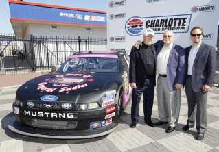 Speedway Children's Charities Executive Director Gen. Tom Sadler (left) was joined by Speedway Motorsports, Inc. Chairman Bruton Smith and Charlotte Motor Speedway President and General Manager Marcus Smith for a surprise unveiling of a special paint scheme honoring Sadler. The car will be run in Friday's NASCAR Nationwide Series Dollar General 300. (CMS/HHP Photo)